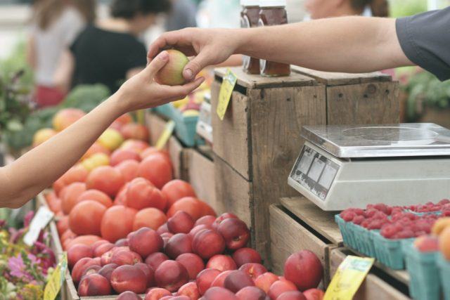 man handing fruit to customer